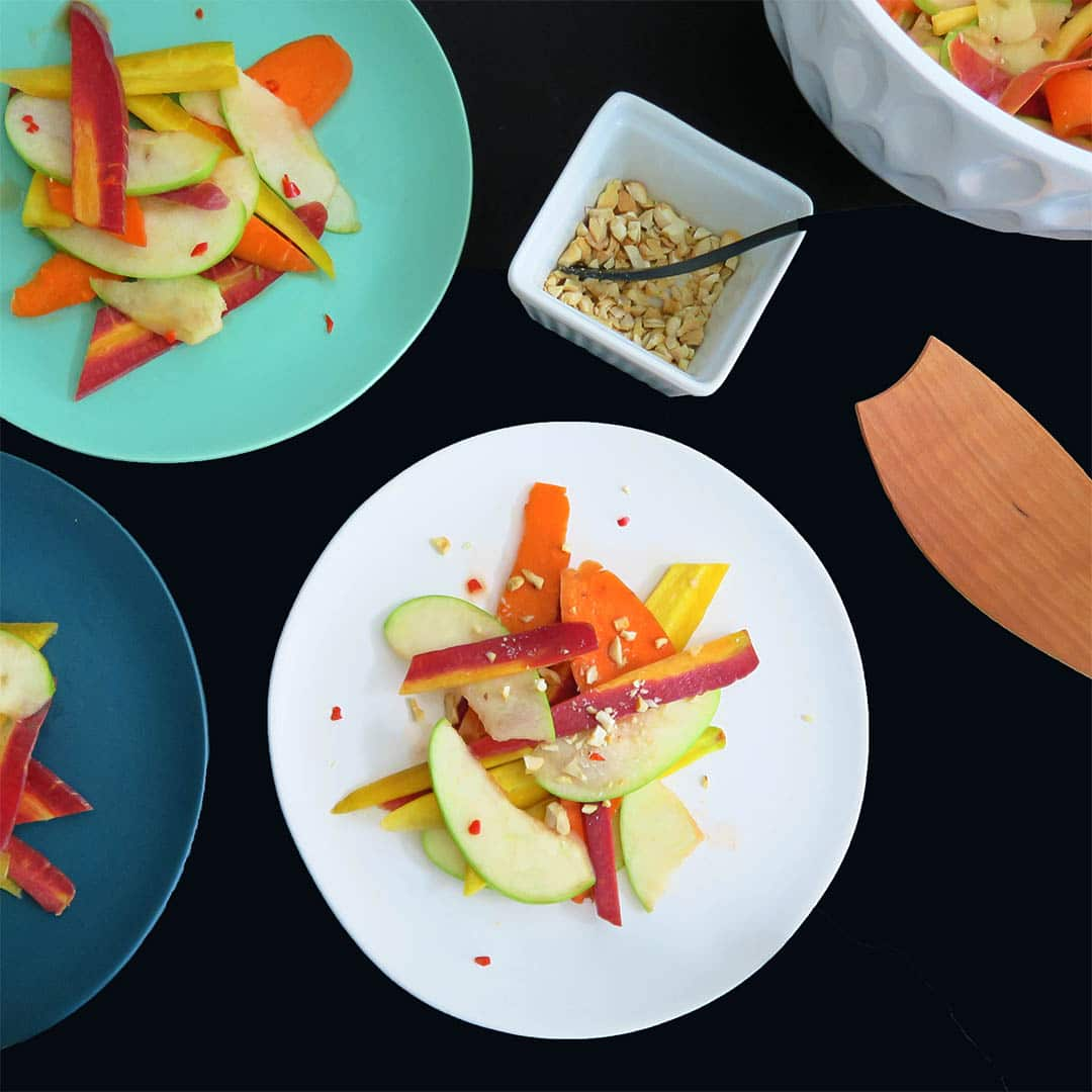 Three colorful plates of Thai Apple Salad on a black background, with a wooden serving spoon and a bowl of crushed peanuts for topping