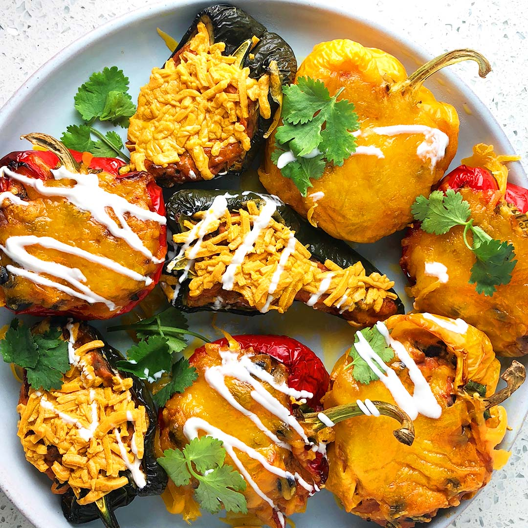 A colourful array of stuffed peppers, green, yellow, and red, topped with cheese, sour cream, and cilantro. From the recipe: Stuffed Pepper Three Ways - Vegan, Vegetarian, Omnivore